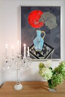 Modern artwork on wall above lit candles in crystal candelabra and vase of hydrangeas on sideboard
