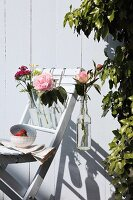 Bottles of flowers hanging on garden chair against white wooden wall