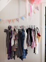 White clothes rail holding girl's clothing and pastel bunting hung on wall