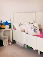 Girl's bedroom with white, extendible bed, scatter cushions and retro-style bedside table