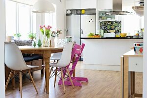 Classic shell chairs and pink Tripp Trapp chair at wooden table in front of counter in open-plan kitchen