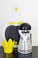 Whimsical salt shaker and yellow, plastic egg cup in front of painted chopping board
