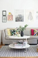 Round side table in front of grey sofa on rug with retro pattern; framed pictures on wall