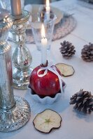 Lit candle in pomegranate used as candlestick, pine cones and dried sliced of apple on table with white táblecloth