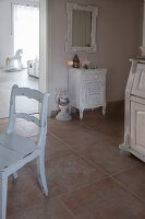 White chair and shabby-chic cabinet on large floor tiles in hallway