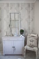 Old window frame on top of white-painted cabinet and kitchen chair against ornamental wallpaper