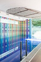 Indoor pool with colourful graphic wall mosaic and lights in metal frame