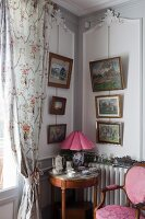 Round, Rococo-style side table below pictures on walls in corner