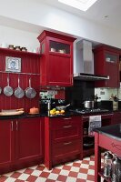 Red-painted kitchen cabinet in country-house kitchen with chequered floor