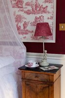 Table lamp with red fabric lampshade on bedside cabinet against red and white toile de jouy wallpaper