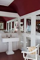 Vintage pedestal sink next to fitted cupboards with mirrored door panels and armchair in bathroom with dark red walls