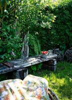 Shady seating area in garden with weathered wooden bench and patterned picnic blanket in foreground