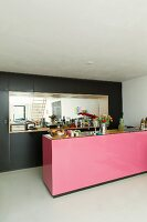 Pink kitchen island in front of black fitted cupboards with mirrored niche
