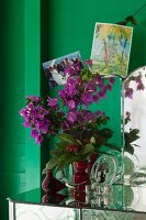 Mementoes and vase of bougainvillea on antique mirrored table against green wall