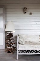 Maritime-style lamp base made of crossed pieces of driftwood next to ornate bamboo bench on white wooden veranda