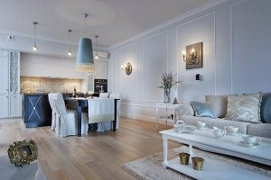 Elegant living-dining room in shades of pale blue and cream with open-plan fitted kitchen in background