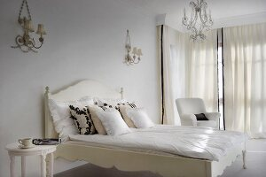 Elegant, white bedroom with period furniture, ornate sconce lamps and chandelier