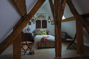 View of bed between rustic wooden beams in converted attic with pitched roof