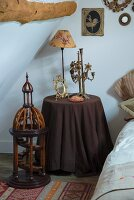 Brass candelabra and vintage table lamp on bedside table with dark brown tablecloth next to wooden architecture model on floor