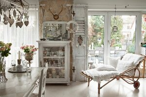Cushions with white lace covers on bamboo chaise in front of French windows