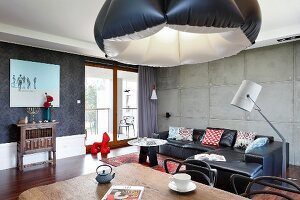 Eclectic style in open-plan interior with inflatable lampshade, black leather couch and exposed concrete wall