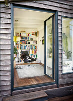 Wooden house with open terrace doors and view into interior with leather armchair in front of bookcase