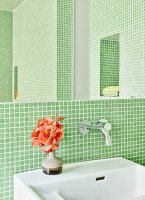 Bathroom with green mosaic tiles and vase of flowers on sink