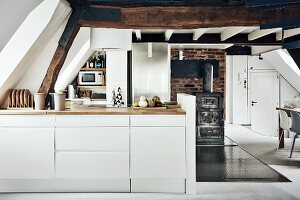 Compact kitchen in open-plan attic interior in historical building