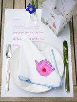 A summer place setting – a fabric napkin with a teapot motif and a lantern on a piece of paper with a poem