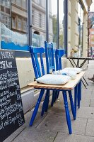 A bench made from three blue wooden chairs and a wooden plank in front of a restaurant