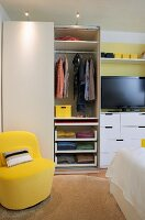 Storage space in bedroom with practical wardrobe divisions; yellow easy chair as sunny accent in ecru and white colour scheme