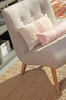 Fifties-style, ecru easy chair and scatter cushions on sisal rug