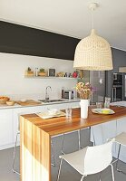 Pendant lamp with wicker lampshade above dining table and bar stools in open-plan designer kitchen