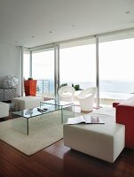 Designer interior with plexiglas furniture, orange accents and sea view