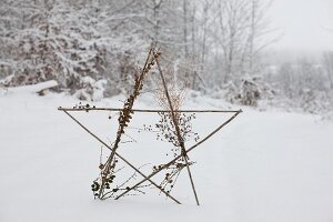 Star made from twigs decorated with dried flowers and larch cones in snowy landscape