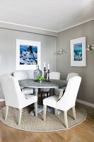 Dining area in corner of pale grey room with white upholstered chairs around round table on sisal rug