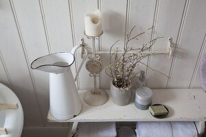Enamel jug, candlestick and flowering branches in ceramic beaker on old wooden bench in shabby-chic bathroom