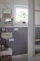 Small bathroom with grey wooden wainscoting and old window used as shower screen