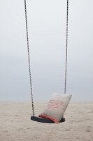 Cushion with crocheted seagull motif on swing on beach