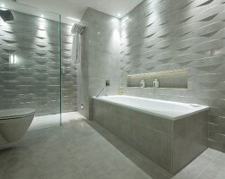 Bathtub, toilet and shower area in designer bathroom with marble tiles and 3D structured tiles