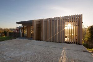 Sun setting behind modern, architect-designed house with wooden slatted structure on facade