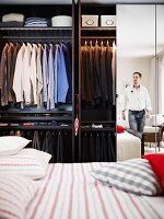 Men's clothing in a wardrobe with mirrored doors with a double bed in the foreground