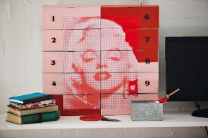 Shoeboxes in shades of red decorated with portrait of Marilyn Monroe used as practical storage solution