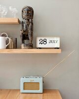 Retro radio below African sculpture on wooden shelf mounted on wall painted pale grey