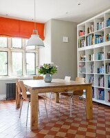 Solid wooden table and chairs on vintage chequered floor with orange Roman blind on window in background