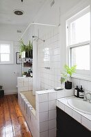 Washstand and bathtub with half-height, tiles partition walls and varnished wooden floor in bathroom of period apartment
