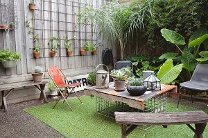 Old wooden bench and hand-made table in courtyard decorated with many potted plants and artificial grass rug