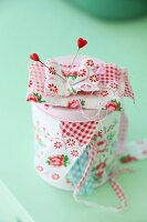 Romantic tin of sewing utensils with heart-headed pins and scraps of rose-patterned fabric