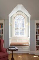 Comfortable, sunny window seat in niche of arched window in library