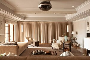 Spacious home cinema with floor-length curtains and comfortable upholstered furniture in elegant, country-house interior